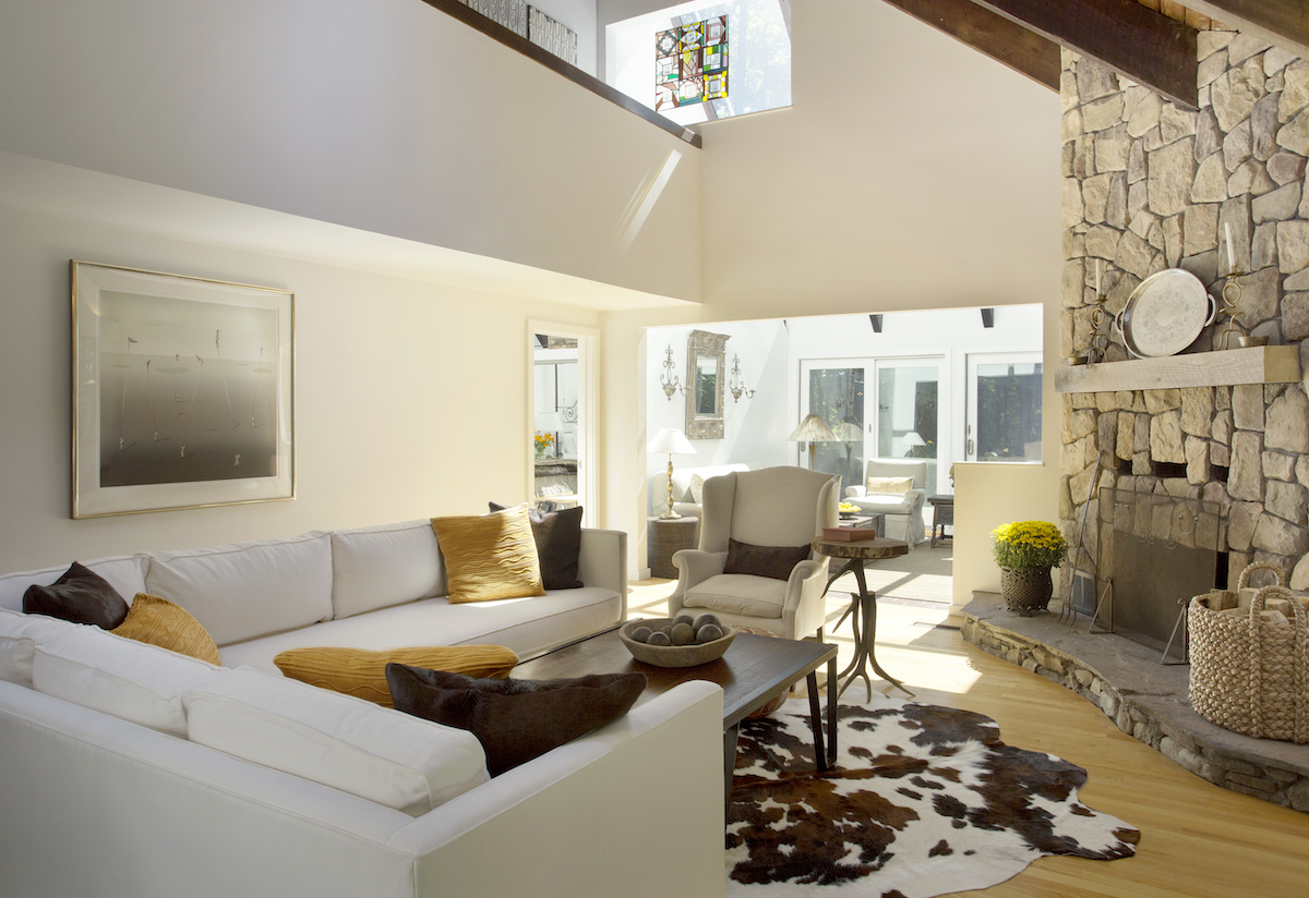 living-room-design-cow-print-rug-stone-fireplace